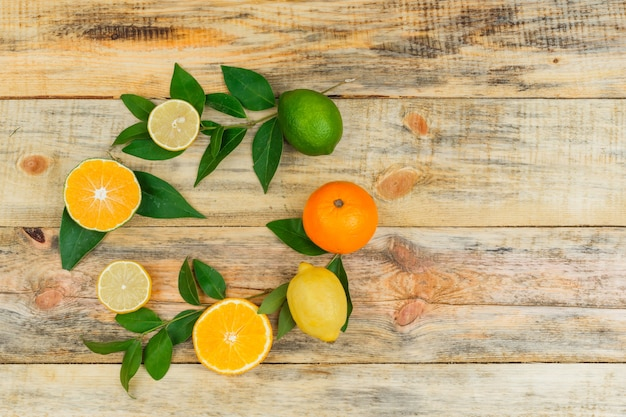 Set of leaves and citrus fruits on a wooden board