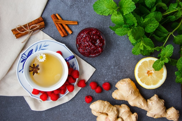 Set of lemon, raspberries and raspberry jam in saucers, ginger, mint leaves, dry cinnamon and a cup of chamomile tea on a cloth