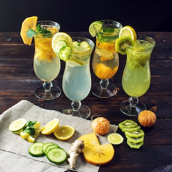 Set lemonade with ice in glass hurricane with tropical fruits
