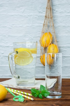 Set of lemons, leaves and carafe of lemon on a white cloth on a wooden and white surface. side view.