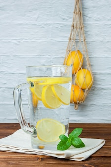 Set of lemons, leaves and carafe of lemon on a wooden and white surface. side view. space for text