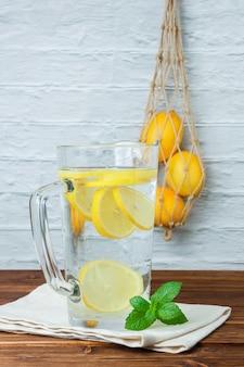 Set di limoni, foglie e caraffa di limone su una superficie di legno e bianca. vista laterale. spazio per il testo