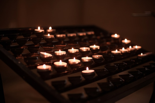 Set of lighted candles in church. hope, praying concept.