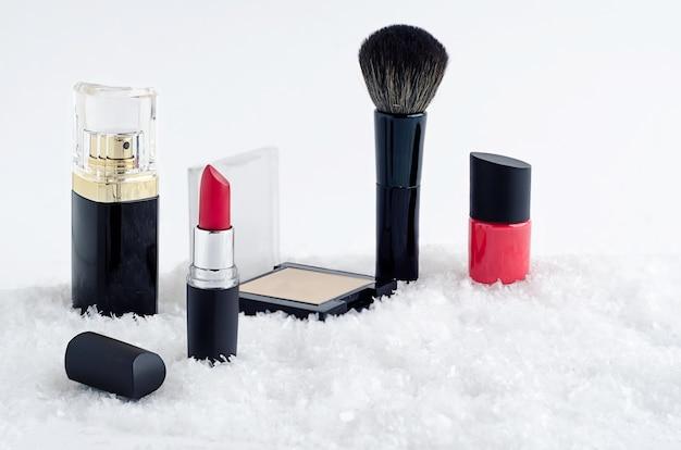 高級化粧品、赤い口紅、マニキュア、パウダー、ブラシ、香水をセットします。メイクアップのための流行の化粧品。