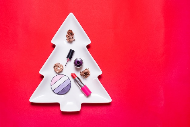 Set of make up accesories on cristmas tree, copy space, red background