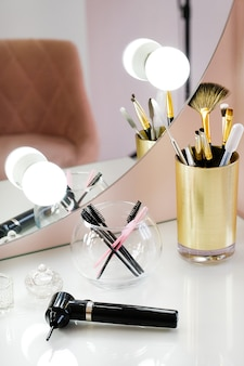 A set of makeup artist brushes for professional makeup and a mixer for mixing paint in front of a mirror