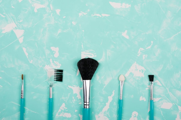 Set of makeup brushes on a blue marble background