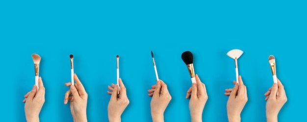 Set of makeup brushes in female hand on the background of eye shadow sets.