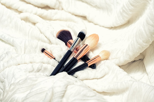 A set of makeup brushes on a soft light cloth.