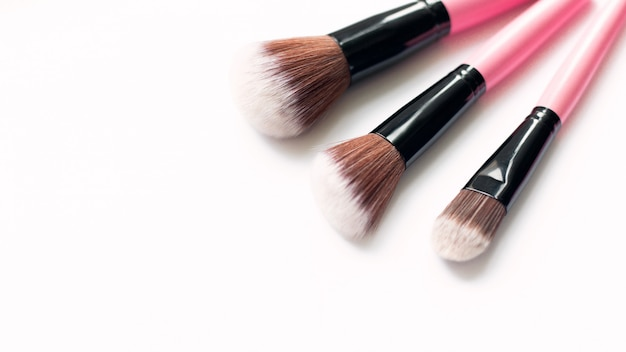 Set of makeup pink brushes on white background. top view, flat lay