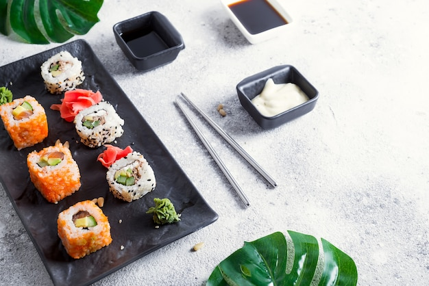 Set of maki roll and green leaves palm on stone table.