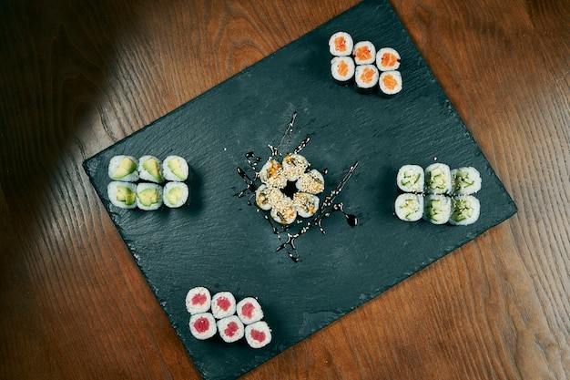 Set of maki roll sushi with cucumber, salmon, eel, tuna on black sltae board on wooden table. japanese cuisine. top view