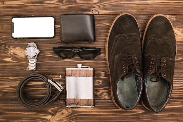 Set of male shoes near smartphone and accessories