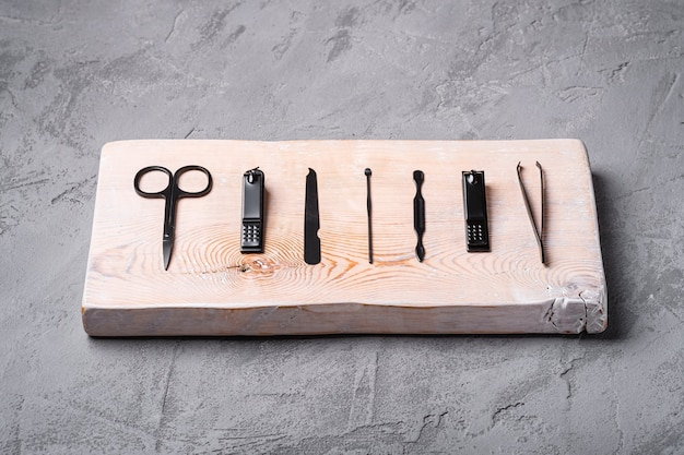 Set of manicure, pedicure tools and accessories on wooden board, stone concrete background, angle view
