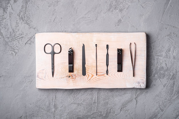 Set of manicure, pedicure tools and accessories on wooden board, stone concrete , top view