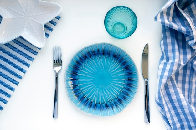 Set in marine style - empty plates in shape of starfish, glass, fork and knife on striped napkins on toning in classic blue color