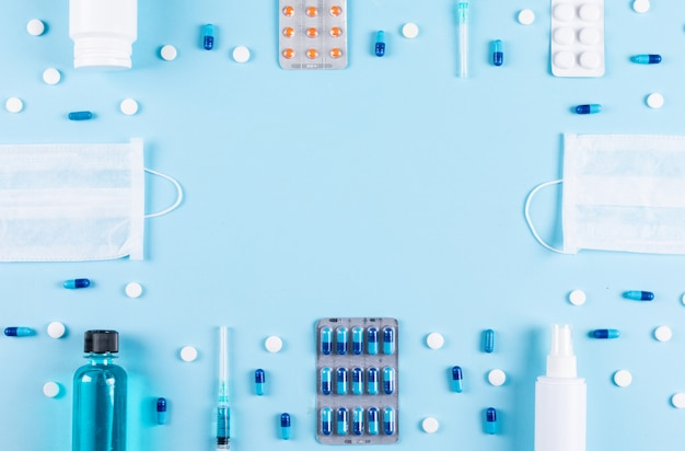 Set of masks, spray, pill bottle, needles and pills spread around on a light cyan background. top view. space for text