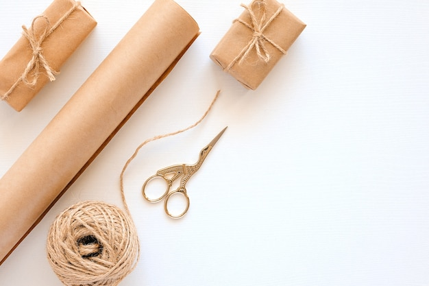 Set of materials for packing holiday gifts. kraft paper, jute twine, scissors, boxes on white background