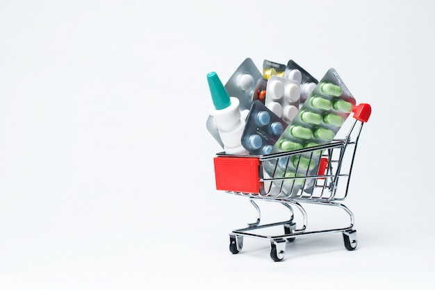 Set of medicine in a supermarket cart on a white background. concept of treatment and prevention