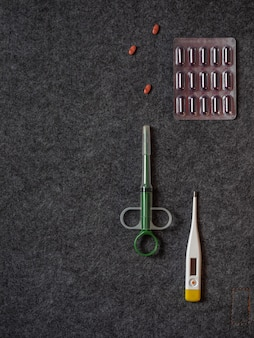 Set of medicines and tools for the treatment of infection, thermometer and pills on a dark background