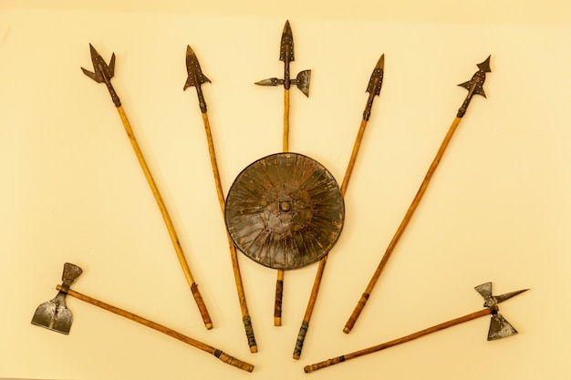 A set of medieval weaponry. spears, axes, shield on beige background.
