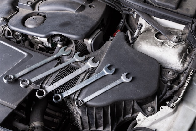 A set of metal spanners of different sizes lies under the hood of the car on an oil cooler. concept of car repair and tools in car service