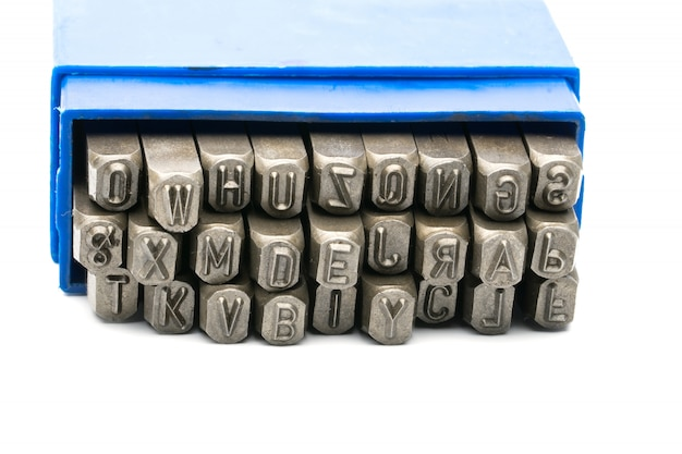 Set of metal stamp alphabet punch in blue plastic box isolated on white background
