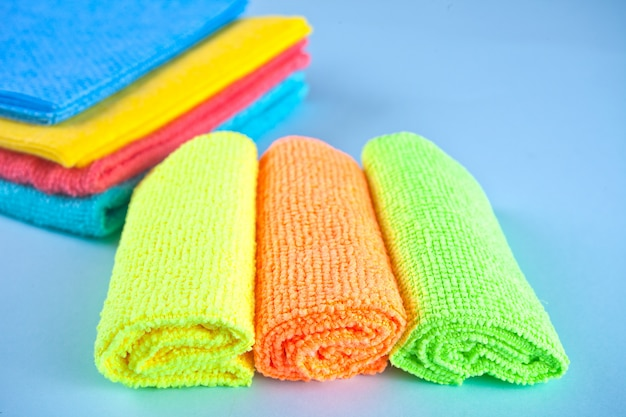 Set of microfiber cleaning towels and sprayer over blue background