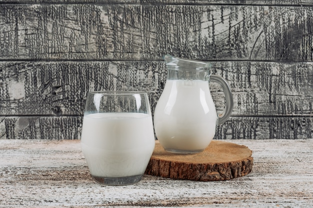 Set of milk carafe and glass of milk in a wooden slice on a gray wooden background. side view.
