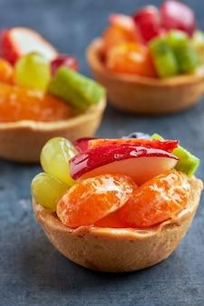 Set of mini premium fresh fruit desserts on a sponge cake base on wooden table.