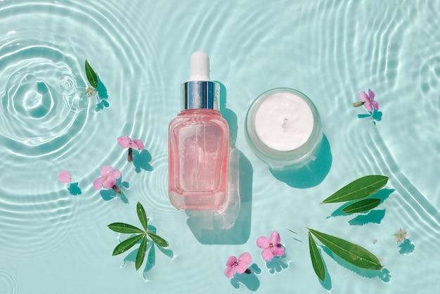 Наносите увлажняющие косметические средства на воду с каплями. стеклянная бутылка для сыворотки и банка для крема на поверхности аква с волнами в солнечном свете. концепция рекламы органического увлажняющего ухода за кожей, спа.