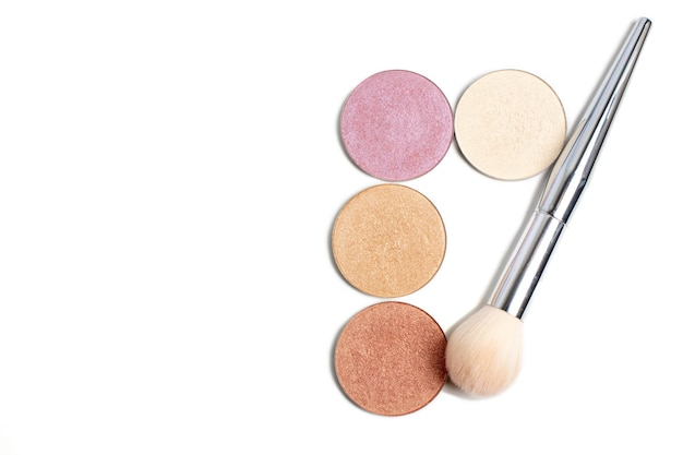 Set of multicolor face highlighter refill with a brush over a white background