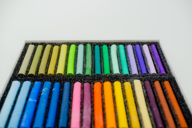 Set of multicolored pastel crayons in openartist box on a white background, top view.