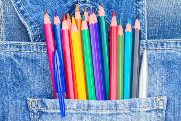 Set of multicolored pencils in blue jeans pocket