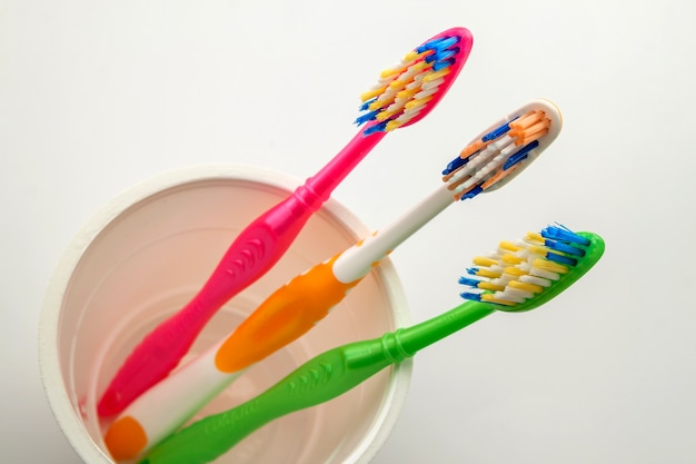 Set of multicolored toothbrushes in glass