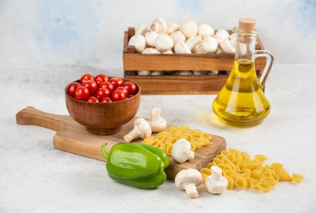 Set di funghi, olio extra vergine di oliva, pasta, pomodorini e peperoncino su un pezzo di marmo.