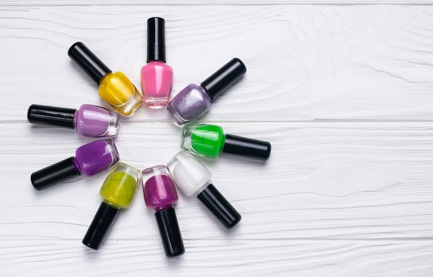 Set of nail polish bottles in different color on white wooden background