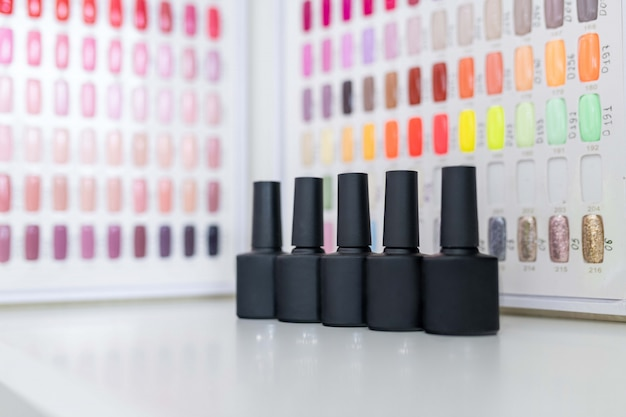 A set of nail polishes on the  of a multi-colored palette of shades of color