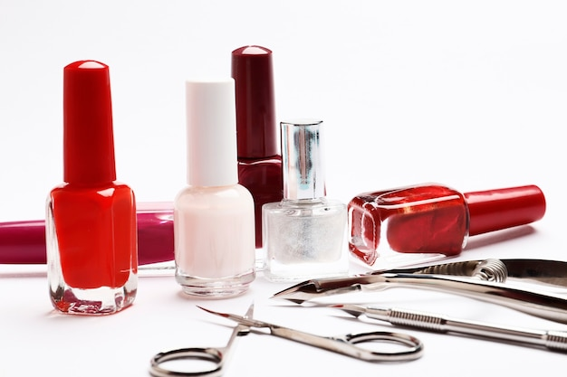 Set of nail polishes and tools for manicure on a white background.