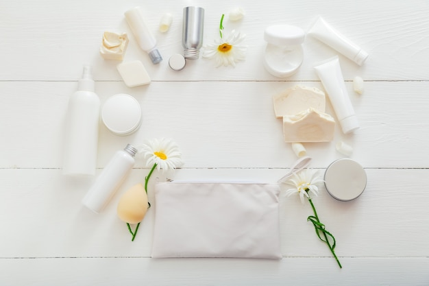 木製のテーブルに白いパッケージでナチュラルバススキンケア製品を設定します。家庭での美容健康のためのスパ化粧品。化粧品バッグ、トイレタリー、花、石鹸、保湿クリーム。モックアップフレームコピースペース。