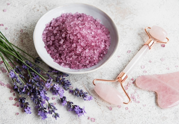 Set of natural organic spa cosmetic with lavender. flat lay bath salt and face roller, on marble background. skin care, beauty treatment concept