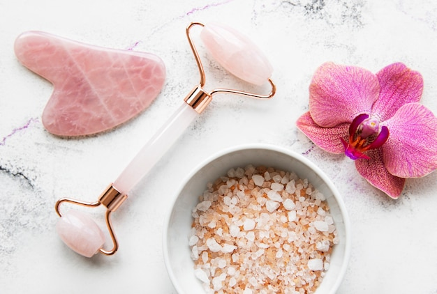 Set of natural organic spa cosmetic with orchid flowers. flat lay bath salt, face roller, orchid flowers on marble background. skin care, beauty treatment concept