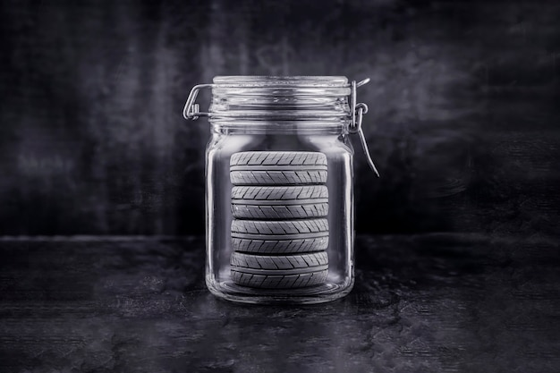 A set of new car tires. seasonal storage of wheels, in a glass jar, as an idea to illustrate the service. black background.