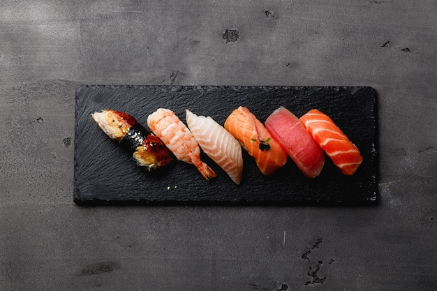Set of nigiri sushi served on plate on dark grey background