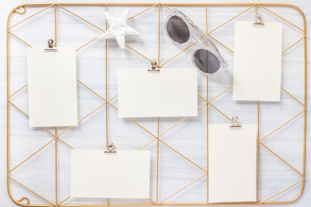 Set of note pad clip frame and starfish with sunglasses on wood table.