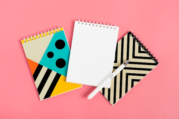 Set of notebooks for notes and pens on pink background place for text flat lay