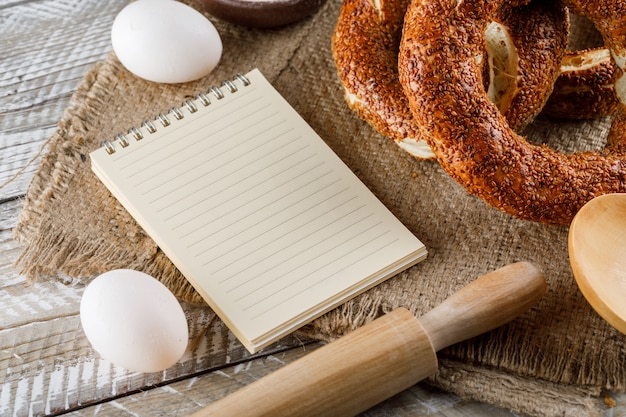 Set of notepad, eggs, rolling pin and turkish bagel on a sack cloth and wooden surface. high angle view.