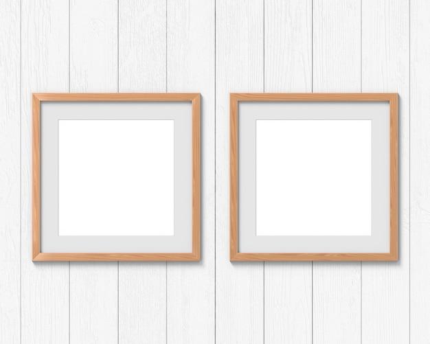 壁に掛かっている境界線を持つ2つの正方形の木製フレームモックアップのセット。画像またはテキスト用の空のスペース。 3dレンダリング。