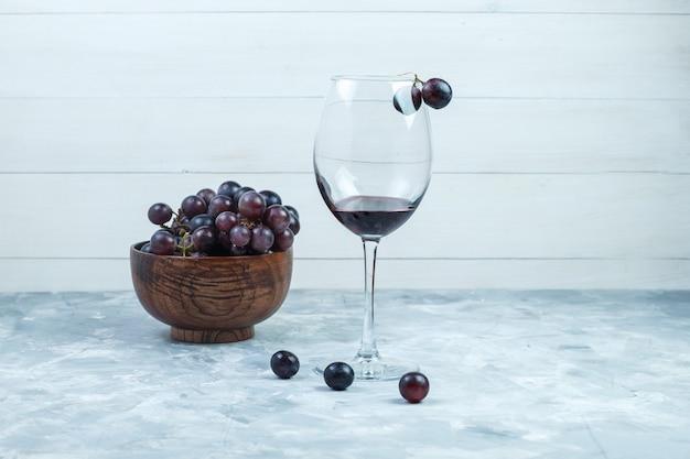 汚れた灰色と木製の背景の上の粘土のボウルにワインと黒ブドウのグラスのセットです。側面図。