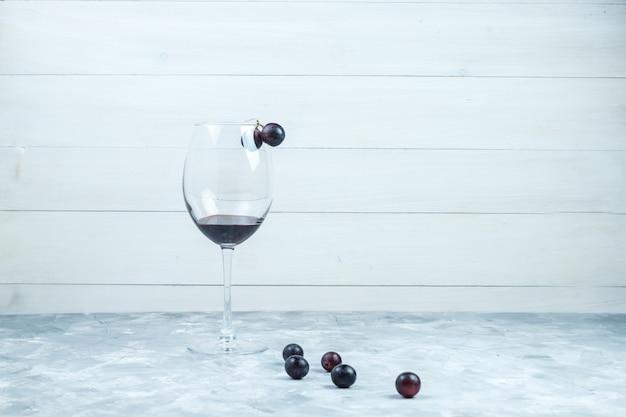 Набор бокала вина и черного винограда на шероховатом сером и деревянном фоне. вид сбоку.